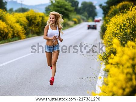 Girl runs on the road - stock photo