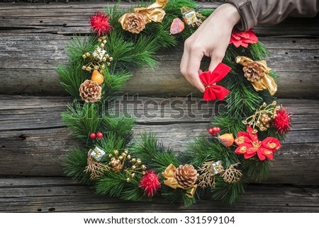 Girl's arm carrying red bow and decorating village log cabin wall with Christmas wreath - stock photo