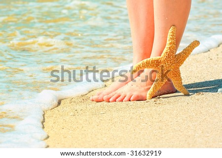 girl's barefoot legs on the sand beach