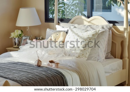 girl's bedroom with ballet shoes and dolls on bed at home - stock photo