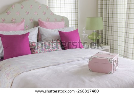 girl's bedroom with pink pillow on green bed and green lamp - stock photo