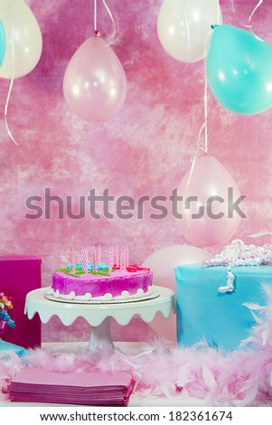Girl's birthday party celebration with cake and balloons  - stock photo