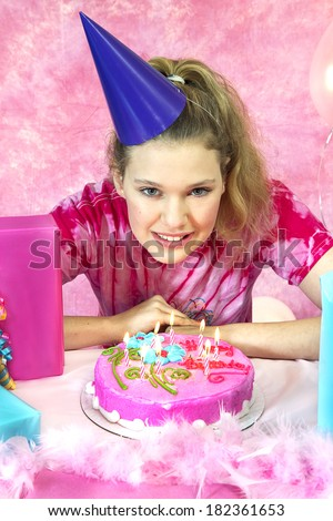 Girl's birthday party celebration with cake and balloons with girl ready to blow out her candles
