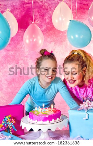 Girl's birthday party celebration with cake and balloons with girls waiting to blow out candles - stock photo