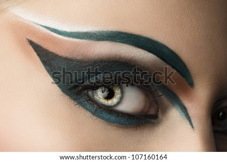 girl's eye closeup with creative green makeup, it looks at right - stock photo