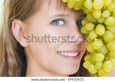 Girl's face with grapes largely - stock photo