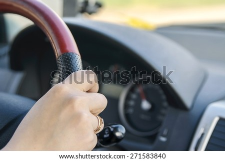 girl's hand holding a steering wheel - stock photo
