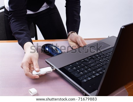 girl's hand inserting usb flash memory into laptop header - stock photo