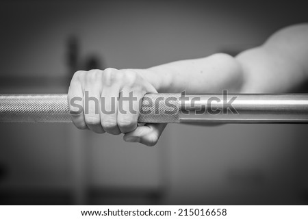 Girl's hand on the barbell. Beautiful girl goes in for sports in the gym. Girl holding a barbell. Gym, strength, fitness - Healthy lifestyle concept. Article about women's fitness. - stock photo
