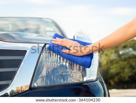 Girl's hand wiping on car's headlight. - stock photo