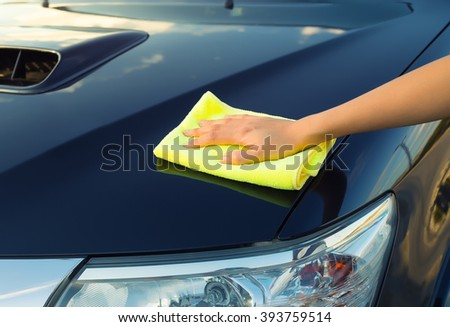 Girl's hand wiping on surface of car. - stock photo