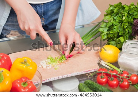 Girl's hand with a knife cutting onions on wooden Board