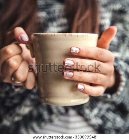 Girl's hands holding a cup of coffee - stock photo