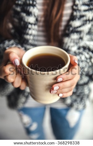 Girl's hands holding a cup of coffee. Stylish manicure and nails - stock photo
