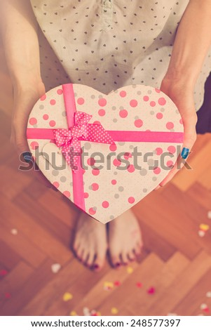 Girl's hands holding heart shaped gift box. Retro colors