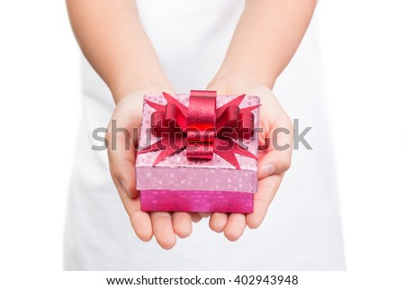 Girl's hands holding shinny pink box of present with shinny red bow on top, white shirt, white background, selective focus on the bow and box leaving shirt and background out of focus - stock photo