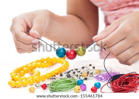 Girl's hands making a necklace with wooden beads - stock photo