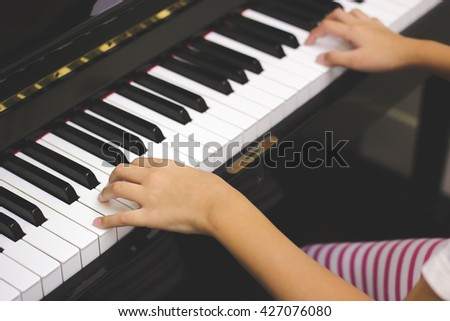 Girl's hands on the keyboard of the piano.soft focus - stock photo