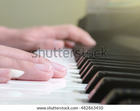 Girl's hands on the keyboard of the piano,Warm color toned image.(selective focus)