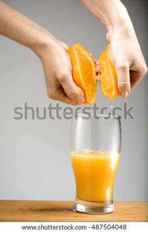 Girl s hands squeezing out juice from orange into glass.