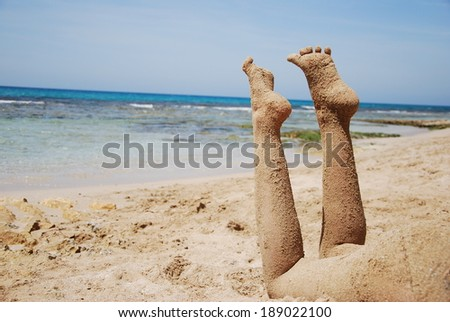 Girl's legs covered in sand on the summer beach