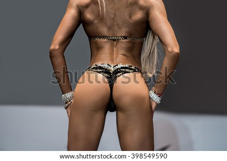 Girl's muscular back and butt. Sexy model in dark bikini. Result of correct time investment. Perfect tanned body. - stock photo