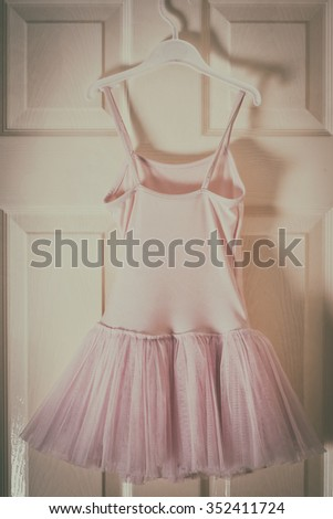 girl's pink ballet  dress hanging on door in bedroom at home