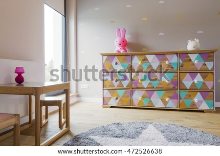 Girl's room interior with a large chest of drawers decorated in pastel triangles