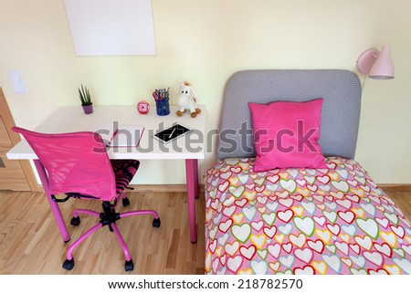 Girl's room with white desk and comfortable bed - stock photo