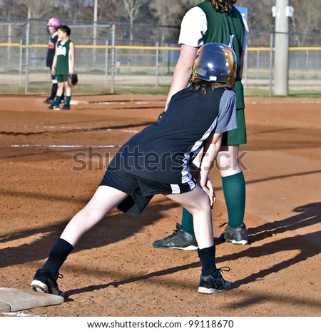 Girl's softball runner on base watching the action. - stock photo