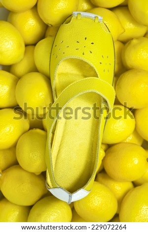Girl's yellow shoe on stack of lemons