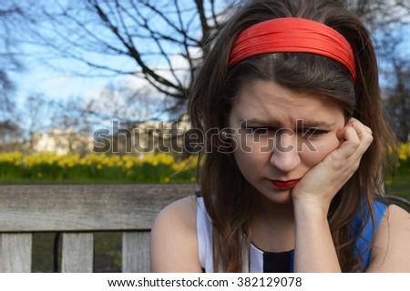 Girl sad on bench - stock photo