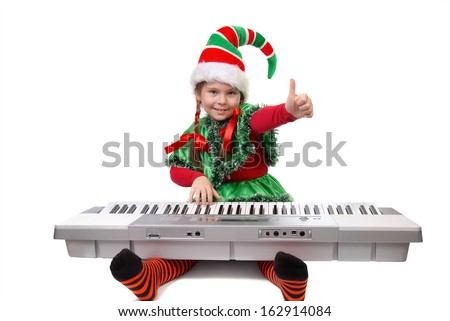 Girl - Santa's elf plays a synthesizer and showing sign OK. Isolated on a white - stock photo