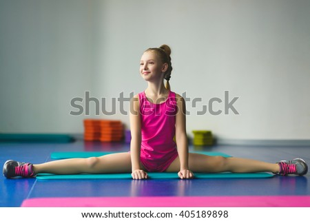 Girl sat and makes stretching or gymnastic exercises in the class for fitness - stock photo