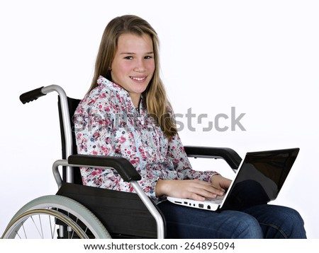 Girl sat in a wheelchair studying with a portable computer - stock photo