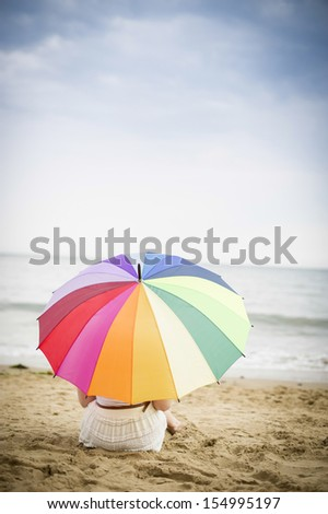 Girl sat under a colourful umbrella on the beach