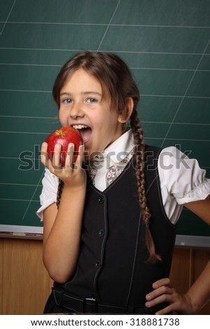 Girl schoolgirl in a black school uniform, a white shirt, with two braids and a red apple on his head and in his hand on a green blackboard - stock photo