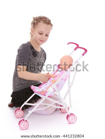 Girl schoolgirl playing with a doll who sits in a wheelchair - Isolated on white background - stock photo