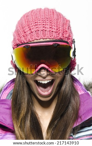 Girl screaming and smiling in winter ski clothing in a studio