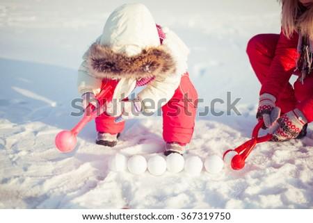 Girl sculpts snowballs - stock photo