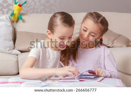Girl secrets. Two girls in pink drawing with a pen in a note-pad smiling and having fun
