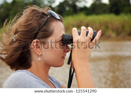 Girl seeing through binoculars at boat ride in the jungle