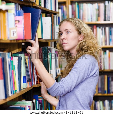 girl selecting book from a bookshelf