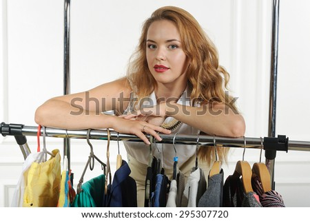 Girl sells clothes hung on hangers and waits for customers against a light background - stock photo