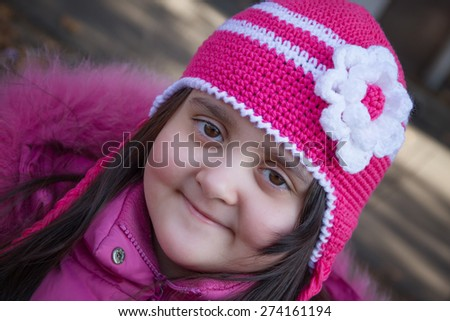 Girl seven years, in the winter, in bright pink knitted hat - stock photo