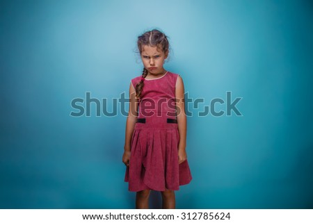 Girl seven years old, European-looking brunette in a pink dress her head and frowned on a gray background, bad mood, anger - stock photo