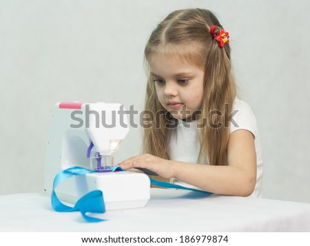 Girl sew on a children's sewing machine. Studio, a white background.