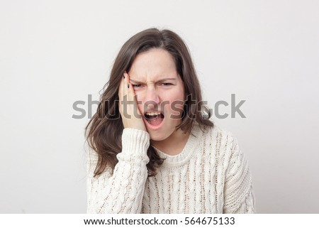 Girl shocked grabs her face. Twinge of toothache