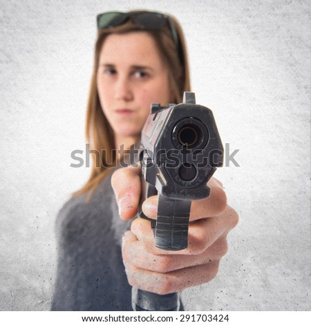 Girl shooting with a pistol over textured background
