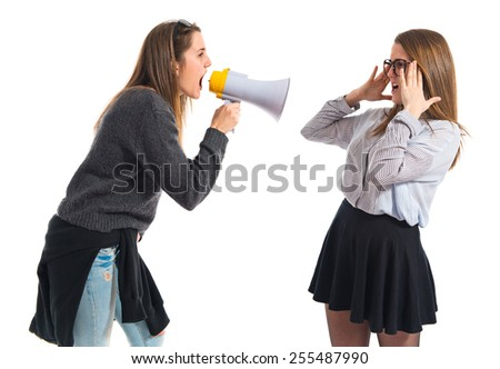 Girl shouting at her sister by megaphone   - stock photo